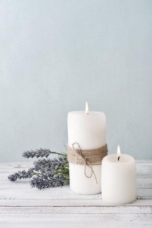 Zwei Kerzen mit lila Blumen auf hellblauem Hintergrund