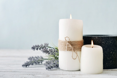 spa still life: Two candles with lavender flowers on light blue background Stock Photo