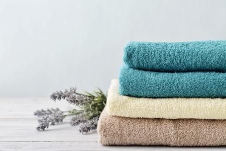 bañarse: Pila de toallas de baño con flores de lavanda en la luz de fondo de madera de cerca