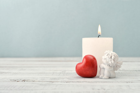heart of stone: Statuette of small  angel with stone heart and candle over light background Stock Photo