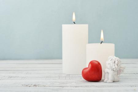 candela: Statuetta di piccolo angelo con cuore di pietra e candele su sfondo chiaro