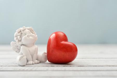 ange gardien: Statuettes de petits anges avec le coeur de pierre sur fond clair