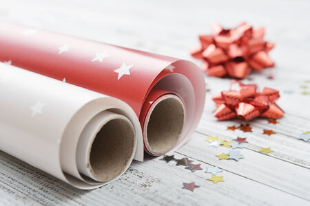 Wrapping paper with bows and confetti on light  background closeup