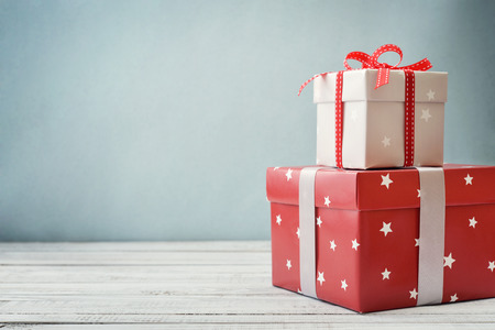 Gift boxes with ribbons and christmas decor on wooden background