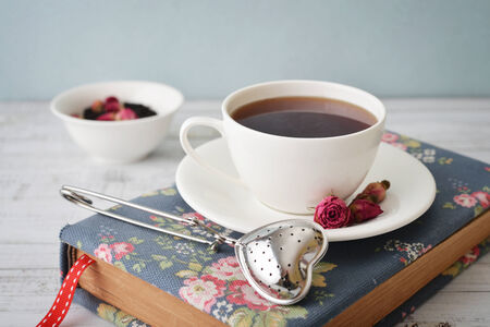 tea strainer: Cup of tea with dry rose buds and tea strainer in the shape of heart