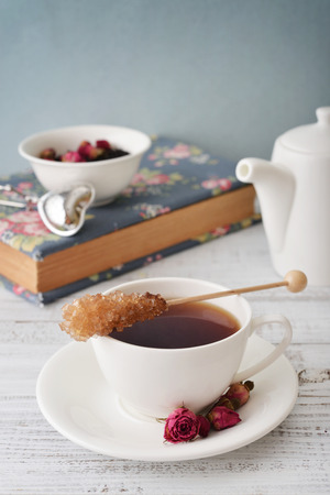 Cup of tea with dry rose buds and candy sugar over blue background photo