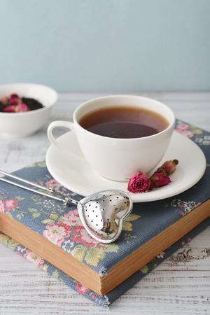 tea strainer: Tea strainer in the shape of heart and cup of tea with dry rose buds Stock Photo