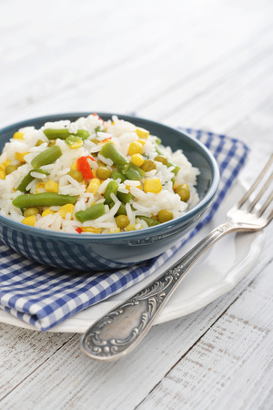 Vegetable risotto on plate with fork on wooden background photo