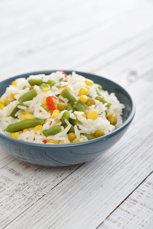 Vegetable risotto on plate on wooden background photo