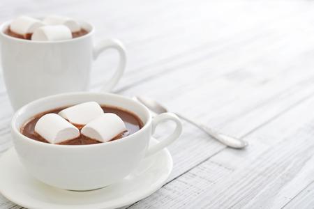 chocolate caliente: Taza de chocolate caliente y malvaviscos en mesa de madera Foto de archivo