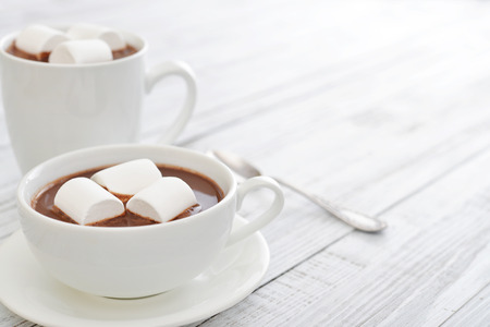 Mug with hot chocolate and marshmallows on wooden table