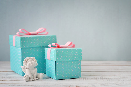 statuette: Blue polka dots gift boxes with statuette of angel on wooden background