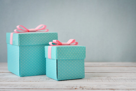 Blue polka dots gift boxes with pink ribbons on wooden background 版權商用圖片 - 35401973