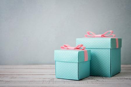 木製の背景にピンクのリボンと青の水玉ギフト ボックス 写真素材