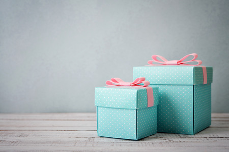 Blue polka dots gift boxes with pink ribbons on wooden background 版權商用圖片 - 35401974