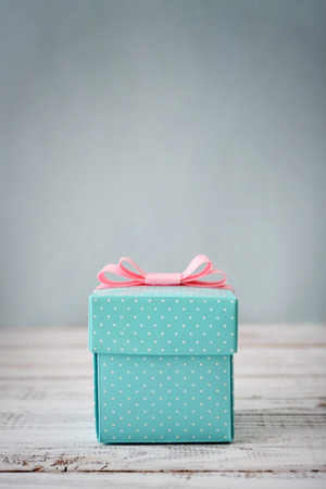 Blue polka dots gift box with pink ribbon on wooden background Foto de archivo