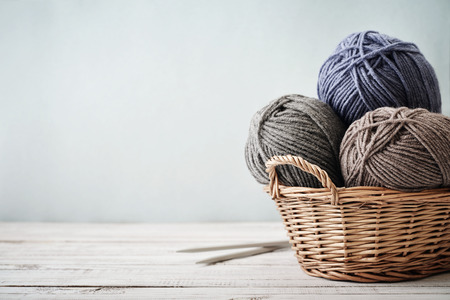 basket embroidery: Wool yarn in coils with knitting needles in wicker basket on light blue background Stock Photo
