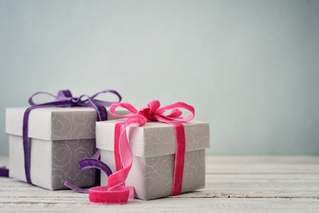dar un regalo: Cajas de regalo con cintas de color violeta y rosa sobre fondo azul