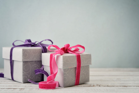 gift background: Gift boxes with violet and pink ribbons on blue background
