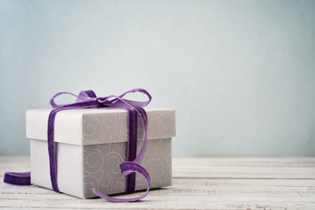 Gift box with violet ribbon on blue background