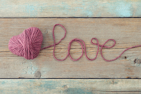 ball of wool: Pink clew in shape of heart and word loveon vintage wooden background Stock Photo