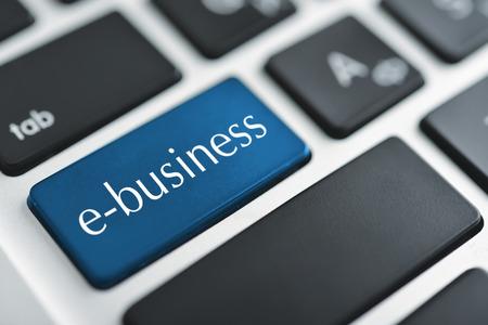 e-business key on a white keyboard closeup. E-commerce concept image Stock Photo