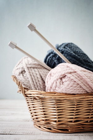 Wool yarn in coils with knitting needles in wicker basket on light blue background 스톡 콘텐츠