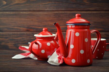 faience: Two red vintage teapots with cup on wooden background Stock Photo