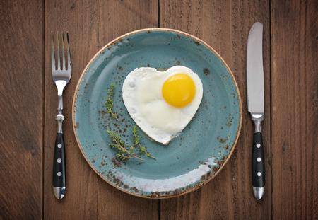 huevo: Huevo frito en forma de corazón en la vista desde arriba la placa azul