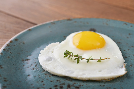 Fried egg in shape of heart on blue plate closeup photo
