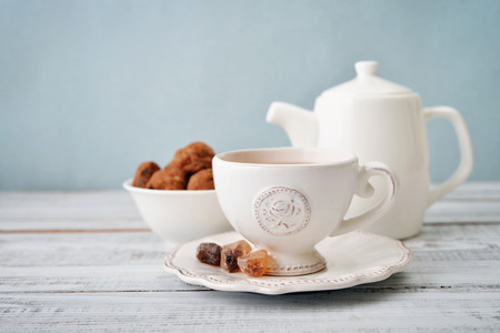 Cup of tea and sugar with cookies  over blue background