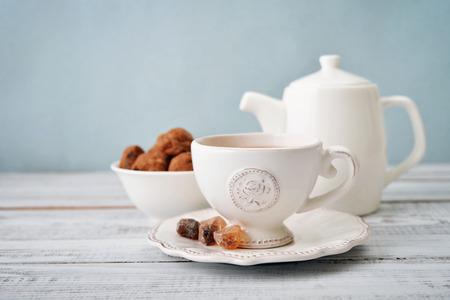 epoca: Taza de té y el azúcar con las galletas sobre fondo azul Foto de archivo