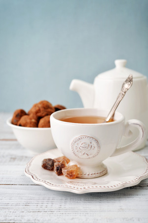 english breakfast tea: Cup of tea and sugar with cookies  over blue background