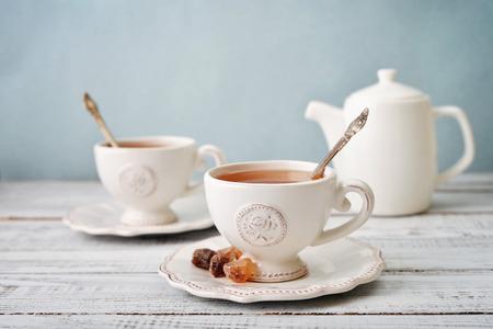 一杯の紅茶と砂糖を青い背景上のティーポット