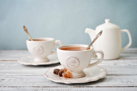 meal time: Cup of tea and sugar with teapot over blue background