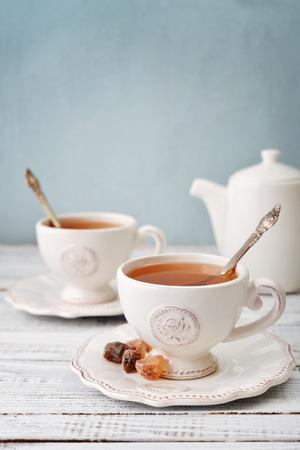 Kopje thee en suiker met theepot op blauwe achtergrond