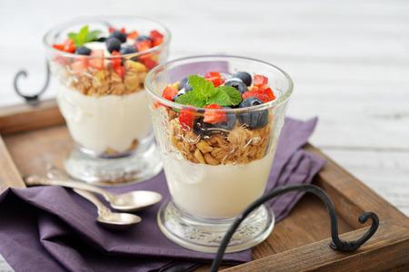 yogurt: Granola con yogur y arándanos y fresas en vidrio en el primer de madera de la bandeja