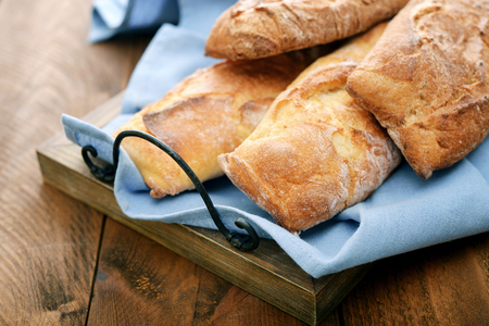 pastry crust: French bread baguettes on vintage wooden tray closeup Stock Photo