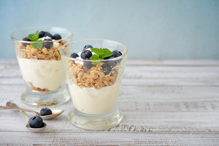Granola with yogurt and blueberry in glass on wooden background Фото со стока