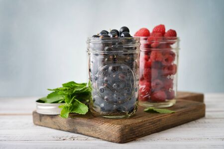 Raspberry and black currant in glass jars on wooden background Stock Photo