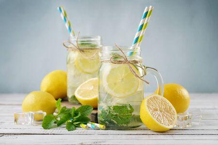 Lemonade with citrus in jars with handles closeup