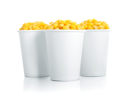 Boiled corn kernels in white paper cups isolated on white