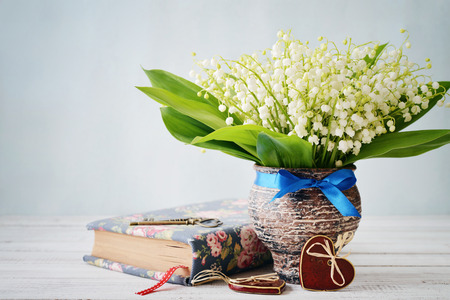ceramic heart: Bouquet of may-lily with book  and ceramic heart on blue background