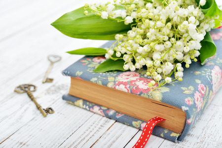 lily flowers: Bouquet of may-lily with book and keys closeup Stock Photo