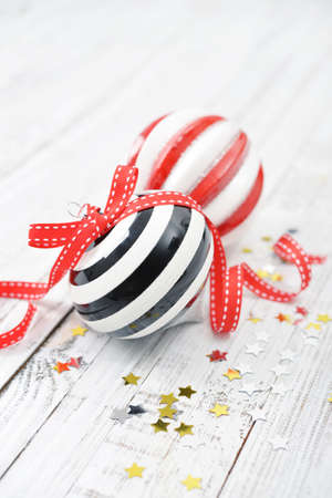 white ribbon: Two christmas striped balls with confetti on wooden background