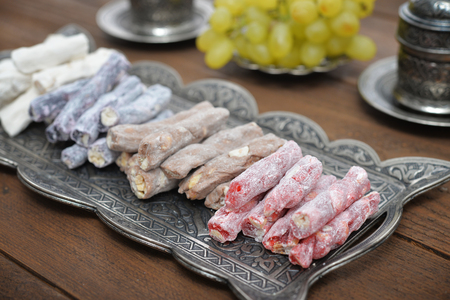 turkish delight: Turkish delight with nuts on metal tray with fresh grape and drinks.