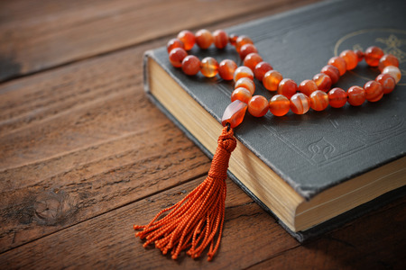 Holy Quran with beads over wooden background close up