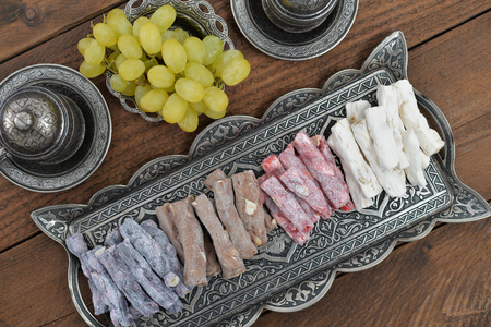 turkish delight: Turkish delight with nuts on metal tray with fresh grape and drinks. Top view