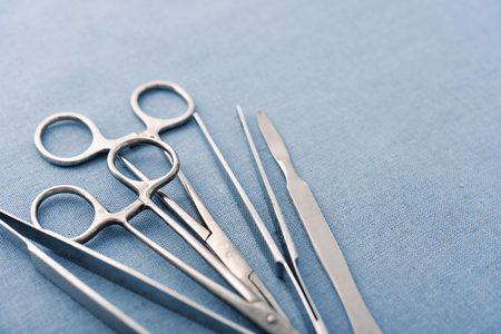 scalpels: Old surgical instruments and tools including scalpels, forceps and tweezers arranged on blue background