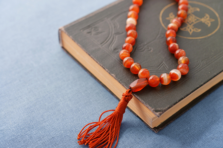 Holy Quran with beads over blue background close up Stock Photo